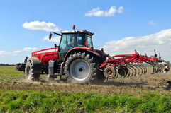Farm tractor plowing the land. Red farm tractor plowing the land Stock Image