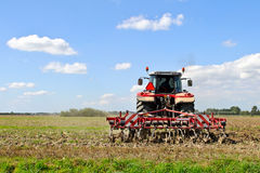 Farm tractor plowing the land Stock Photo