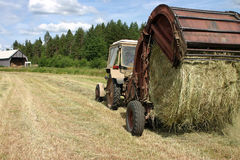 Farm Tractor pulls Round Baler whilst Hay making. Stock Image