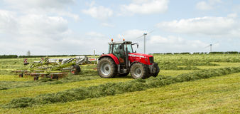 A farm tractor raking hay silage in field Stock Images