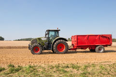 Farm tractor. With a red trailer carrying a grain royalty free stock photo