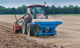 Farm tractor and seeder at work. Farm tractor and seeding macine at work at a Dutch field Royalty Free Stock Images