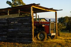 A farm tractor sitting under cover in the early sunshine. Royalty Free Stock Images