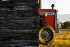 A farm tractor sitting under cover in the early sunshine. Stock Photo