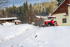 Farm tractor in snow. Farm tractor covered in snow next to house Stock Photography