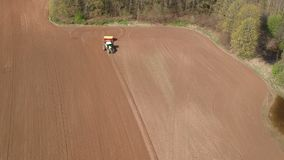 Farm tractor sowing wheat on spring field, aerial stock video