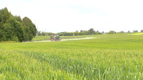 Farm tractor spray summer season green crop plant field stock footage