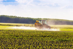 Farm tractor spraying a field. Stock Photo