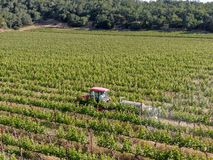 Farm tractor spraying pesticides & insecticides herbicides over green vineyard field. Napa Valley, Napa County, California, USA royalty free stock images