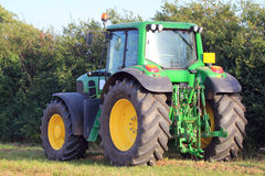Farm tractor standing in field. Stock Photos