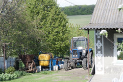 Farm tractor stands in village Stock Photography