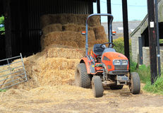 Farm tractor and straw bales. A small farm tractor standing by a stack of straw bales in a dutch barn Stock Images