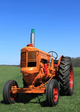 Farm Tractor. Vintage Orange Farm Tractor Parked in Green Farmland in Spring on Blue Sky Background royalty free stock photography