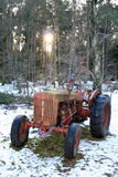 Farm tractor in winter. Farm tractor near woods with light winter snow Royalty Free Stock Images
