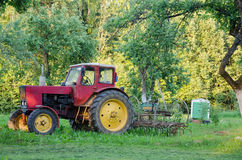 Farm tractor with yellow wheels harow in garden Stock Photos