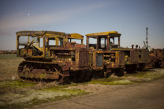 Farm tractors. Old farm tractors at a dumping ground with star trails at night Stock Image