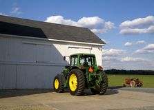 Farm Tractors--Old and New. Two farm tractors, one old, one new, one green and yellow, the other red, parked outside a crisp white barn.  Field is visible in Royalty Free Stock Photography