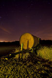 Farm trailer at night. Old farm trailer at a dumping ground with star trails at night light painted yellow Stock Images