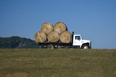 Farm Truck. White farm truck carrying round hay bales Royalty Free Stock Images