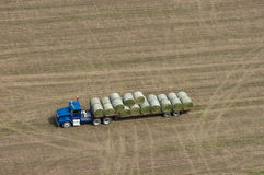 Farm Truck Loading Hay Bales for Dairy Cows. Aerial view of a tractor trailer semi in a farm field and loaded with hay bales to be used for feeding dairy cows Stock Photography