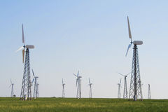 Farm turbines in green field over blue sky Royalty Free Stock Image