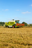 Farm vehicle cutting the crops in summer Royalty Free Stock Images