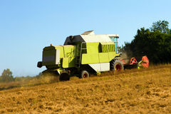 Farm vehicle cutting the crops in summer Royalty Free Stock Photos