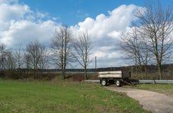 Farm Wagon Along Rural Road. Farm Field and Farm Wagon Royalty Free Stock Images