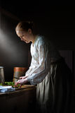 Farm Wife Cooking Dinner, Food. A housewife woman cooking dinner on the farm. The farmer wife is cutting asparagus while preparing dinner or supper for the Royalty Free Stock Image