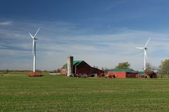 Farm with wind turbines. A farm in the country with two wind turbines Royalty Free Stock Images