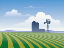 Farm With Windmill. Farm landscape showing rows of crops and silhouette of farm buildings including windmill