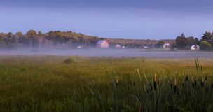 Farm with a wood barn and houses next to a grass field at sunrise. royalty free stock image