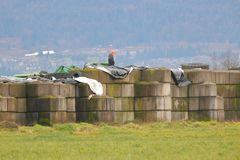 Outdoor Farm Fertilizer Containment. A farm worker stands on top of concrete slabs that contain crop fertilizer stacked on a field stock images