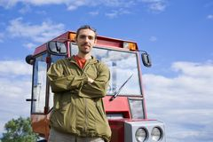Farm worker with tractor. On field in summer day royalty free stock images