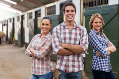 Farm workers arms crossed. Portrait of horse farm workers with arms crossed in stable Royalty Free Stock Photo