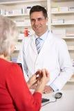 Farmacéutico americano con la mujer mayor en farmacia Fotografía de archivo libre de regalías