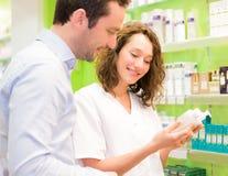 Farmacéutico atractivo que aconseja a un paciente Imagen de archivo