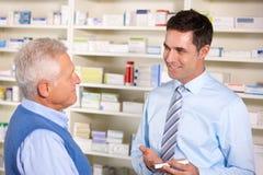 Farmacéutico BRITÁNICO que sirve al hombre mayor en farmacia Imágenes de archivo libres de regalías