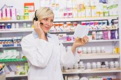 Farmacéutico con el auricular que lee una prescripción Foto de archivo libre de regalías
