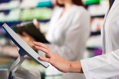 Farmacéutico con el ayudante en farmacia Foto de archivo libre de regalías