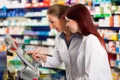 Farmacéutico con el ayudante en farmacia Fotos de archivo libres de regalías