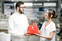 Farmacéutico con el equipo del cliente y de primeros auxilios en la farmacia imagenes de archivo