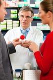 Farmacéutico con los clientes en farmacia Fotografía de archivo libre de regalías