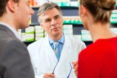 Farmacéutico con los clientes en farmacia Fotografía de archivo