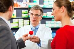 Farmacéutico con los clientes en farmacia foto de archivo