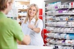 Farmacéutico de sexo femenino con el cliente en el contador Fotografía de archivo libre de regalías
