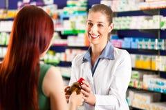 Farmacéutico de sexo femenino en su farmacia con un cliente imagen de archivo libre de regalías