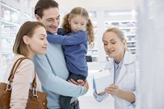 Farmacéutico de sexo femenino profesional que ayuda a la familia foto de archivo libre de regalías