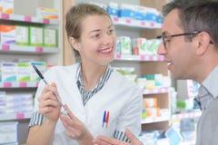 Farmacéutico de sexo femenino que aconseja al cliente sobre uso de las drogas en farmacy moderno fotografía de archivo libre de regalías