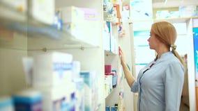 Farmacéutico de sexo femenino que se coloca en el contador en farmacia almacen de video